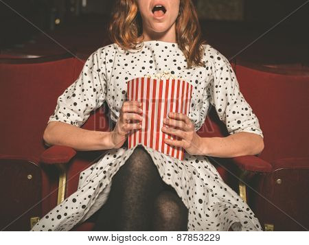 Young Woman On Front Row Of Movie Theater