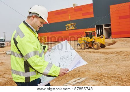 construction engineer builder manager with blueprint drawing project plan at site