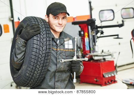 repairman mechanic portrait with tyre in car auto repair or maintenance shop service station with automobile wheel tire