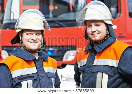 two firefighters in uniform in front of fire engine machine and fireman team