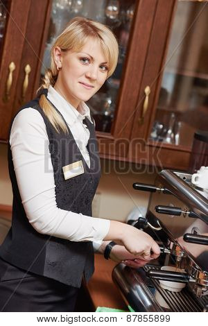 barista woman operating coffee maker machine at the restaurant bar