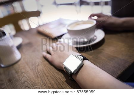 In coffee bar a woman using her smartwatch.