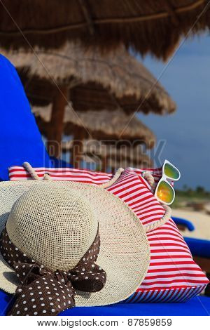 Straw hat, bag and sun glasses on tropical beach