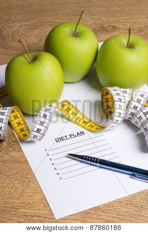 Diet Concept - Paper With Diet Plan, Green Apples And Measure Tape On Table