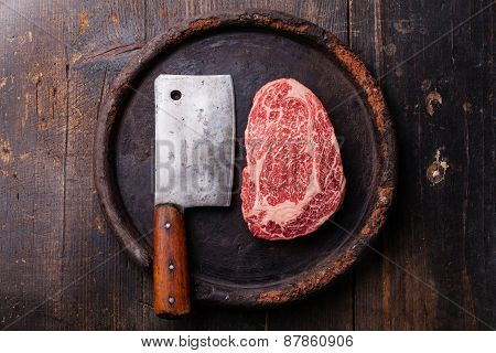 Raw Fresh Marbled Meat Black Angus Steak Ribeye And Meat Cleaver On Dark Background