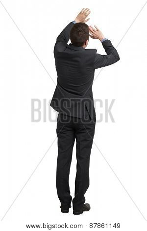 back view of startled businessman in black suit covering himself with his hands. isolated on white background