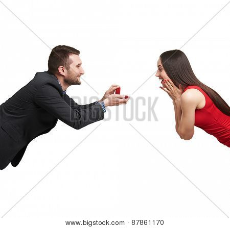 amazed happy woman looking at ring and happy man looking at her. isolated on white background