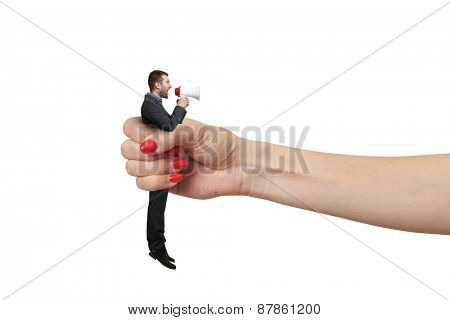 big female hand holding in fist small man and he screaming at megaphone. isolated on white background