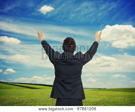 back view of man with hands up against spring nature background