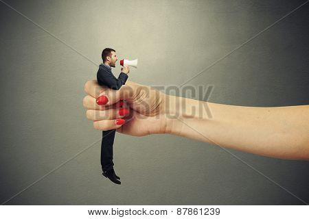 big female hand holding in fist small man and he screaming at megaphone. photo on dark background