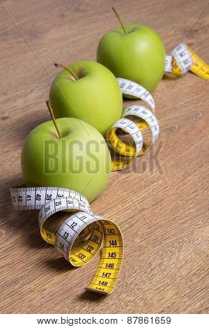 Close Up Of Three Green Apples And Measure Tape On Table