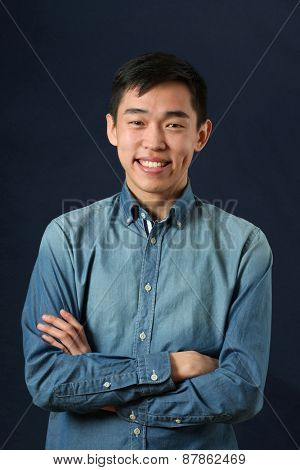 Smiling young Asian man with crossed hands looking at camera