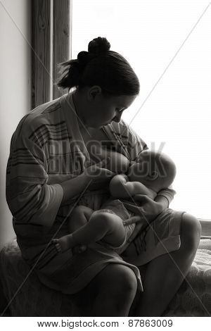 Woman breastfeeding near a window, baby napping, black and white