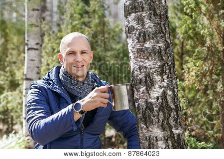 Man in woods collecting birch sap to steel mug