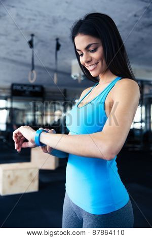 Smiling young woman using activity tracker at gym