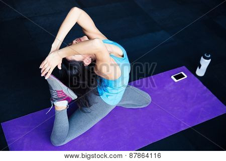 Young woman stretching on yoga mat at gym