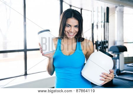 Smiling woman holding plastic container with sports nutrition at gym