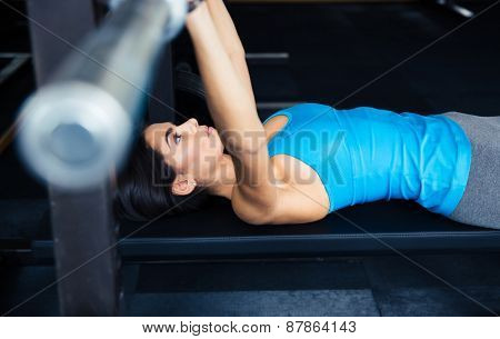 Cute young woman working out with barbell on bench in the gym. Bar Bench Pres