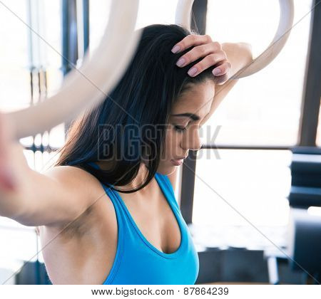 Tired woman with gimnastick rings at gym