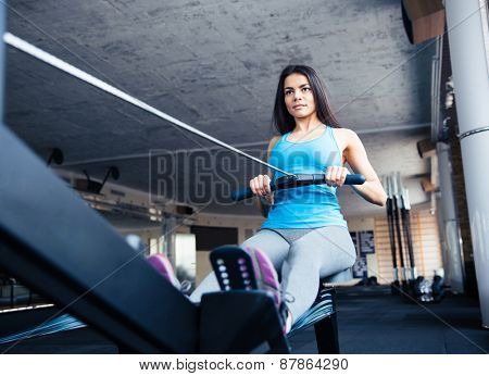 Happy charming woman working out on training simulator in fitness gym