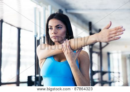 Beautiful woman stretching hands at gym and looking away