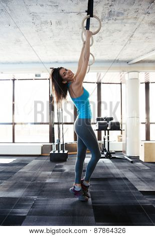 Side view portrait of a happy woman working out on gimnastic rings at gym. Looking at camera