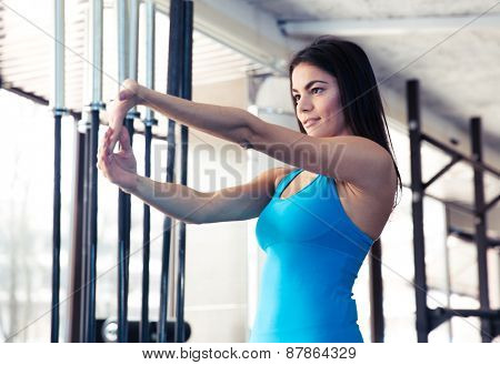 Young attractive woman stretching hands at gym. Looking on hands