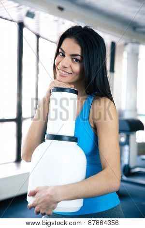 Smiling woman at gym with sports nutrition standing at gym and looking at camera