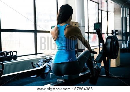 Back view portrait of a young woman working out on simulator at gym