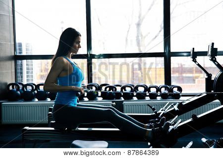 Side view portrait of a beautiful woman working out on simulator at gym