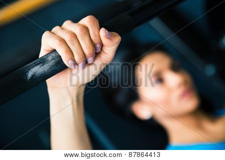 Young fit woman working out with barbell on bench. Focus on barbell