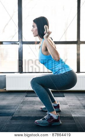 Side view portrait of a young woman doing squats with barbell at fitness gym