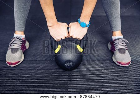 Closeup image of a woman working out with kettle ball at gym