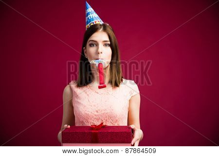 Woman blowing in whistle and holding gift box over pink background. Looking at camera. Wearing in dress