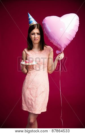 Unhappy young woman holding heart shaped balloon and donut with candle over pink background. Wearing in dress