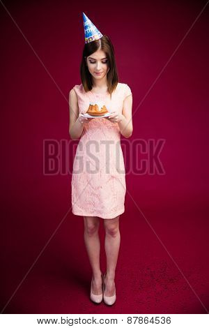 Full length portrait of a happy woman holding cake with candles over pink background. Wearing in dress