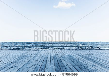Closeup image of a wooden pier with sea