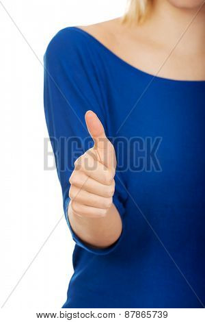 Happy young woman showing thumbs up.
