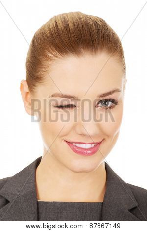 Beautiful businesswoman blinks her eye.