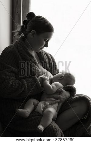 Woman breastfeeding near a window, black and white