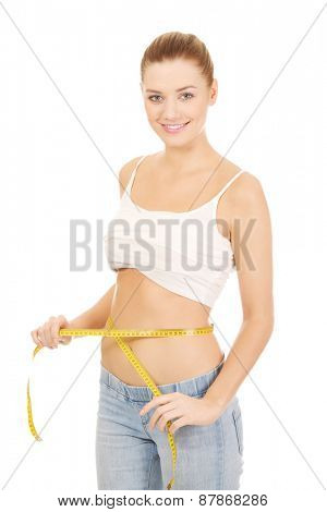 Slim caucasian woman measuring her waist.