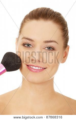 Happy woman applying make up.