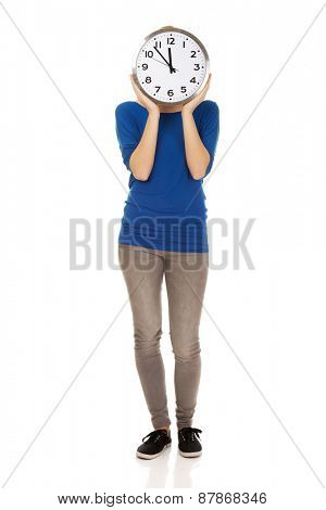 Young casual woman hiding behind a clock.