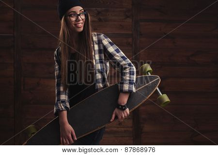 Hipster girl in glasses and with skateboard