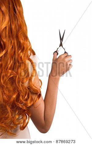 cutting young beautiful red-haired woman's hair with scissors