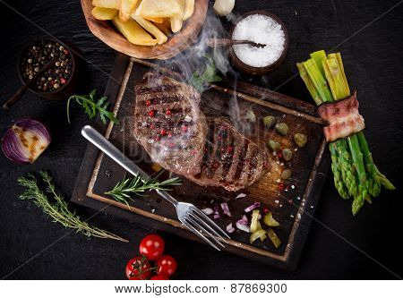 Beef steak on black stone table, close-up