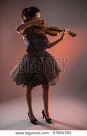 Young woman with violin on dark background