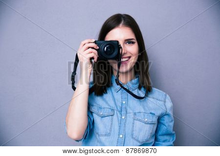 Happy woman making photo on camera over gray background. Looking at camera