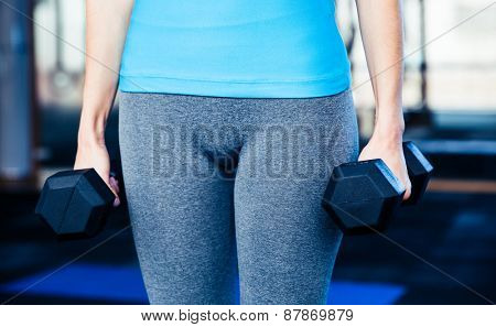 Closeup image of a woman standing with dumbbells at gym