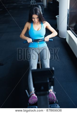 Young woman doing exercise on a simulator at gym